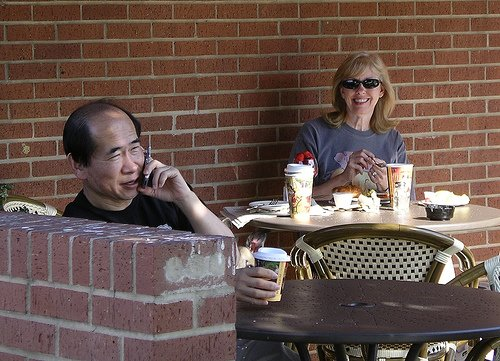 A candid photo of a call phone conversation in a public space.